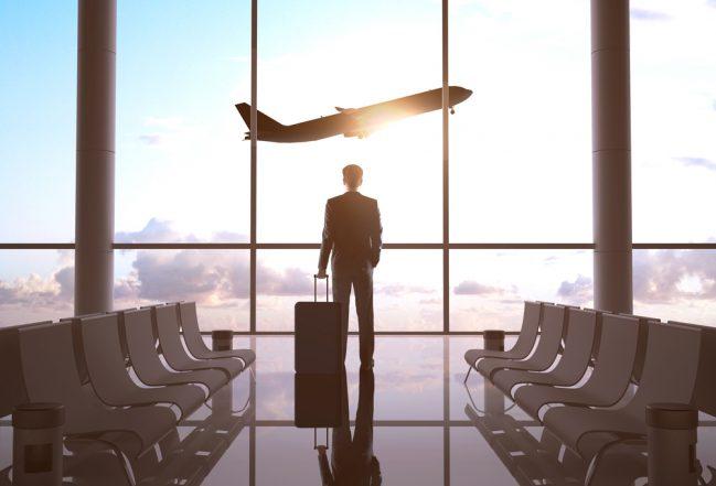 man met koffer op vliegveld